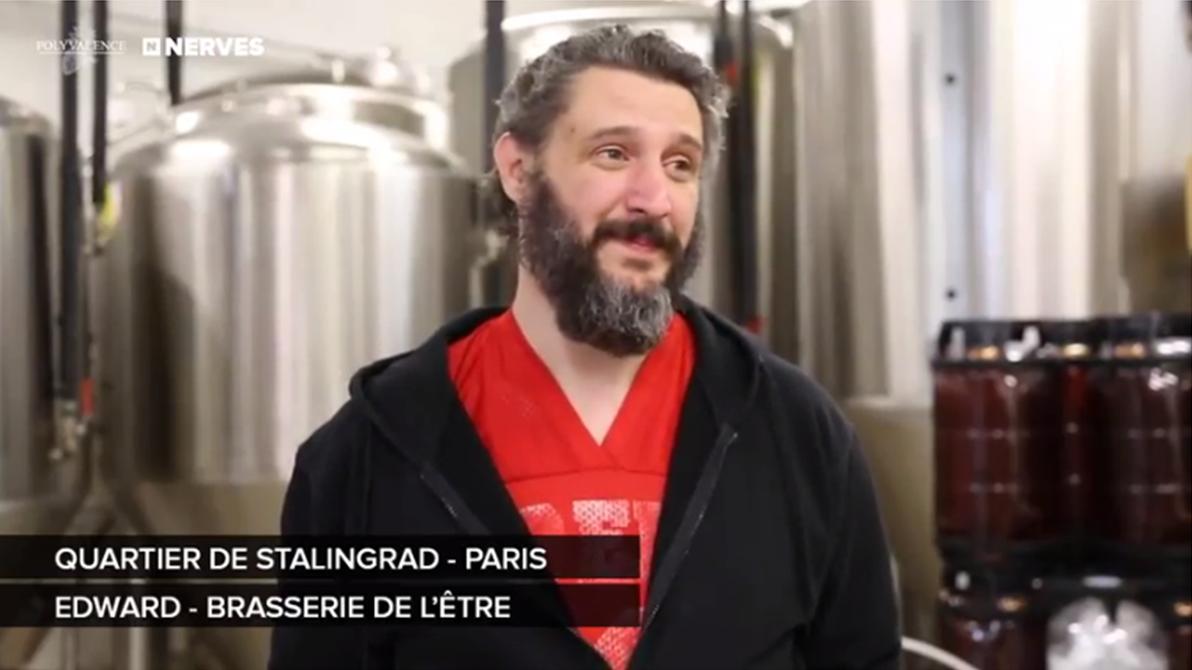 Vidéo youtube : Dans les sous-sols de la Brasserie de l'Être, Edward, grand Monsieur à la barbe grise fournie, l'oeil pétillant et le sourire généreux répond en T-shirt rouge aux questions.