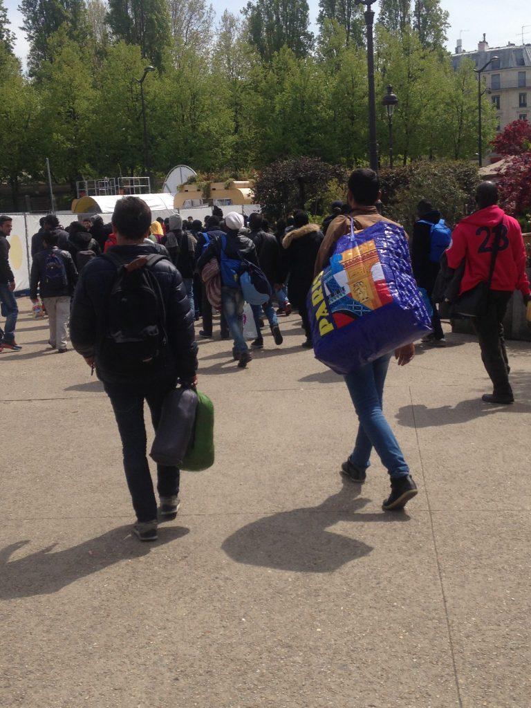 Photographie : Dans Paris, une place entourée d'arbres. Il fait beau. On voit un groupe d'une vingtaine personnes, probablement les réugiés du texte, de dos, portant des sacs de toutes sortes (à dos, de couchage, en plastiques, etc.) avancer vers on ne sait où.