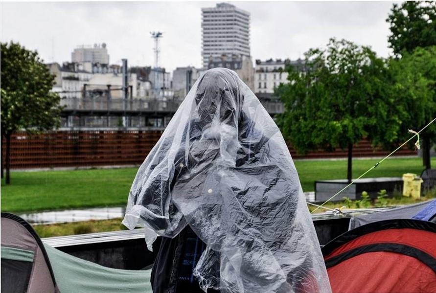 Dans Paris, un jardin. Le ciel est gris. Au loin s'élèven les tours du 13ème arrondissement. Au premier plan, une personne emmitoufflée dans une bâche en plastique transparente se protège de la pluie. On ne distingue pas son visage.