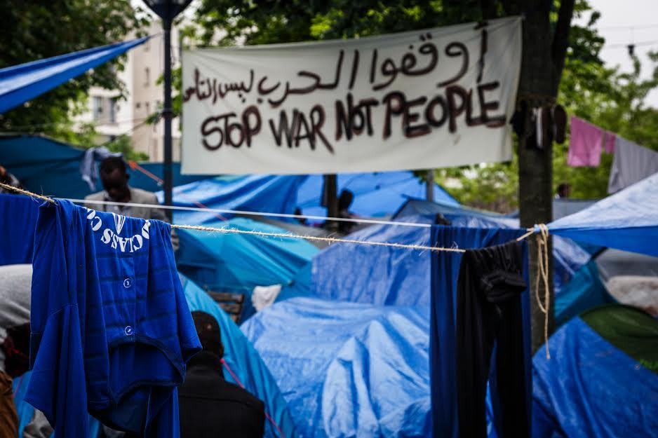 Un fouilli de bâches et de tentes bleues. Il pleut. Entre deux petits arbres, au premier plan (en gros plan) une bannière en drap blanc a été tendue. On peut y lirre, écris à la peinture noire, à la main : STOP WAR NOT PEOPLE. Et la même chose en Arabe au-dessus.