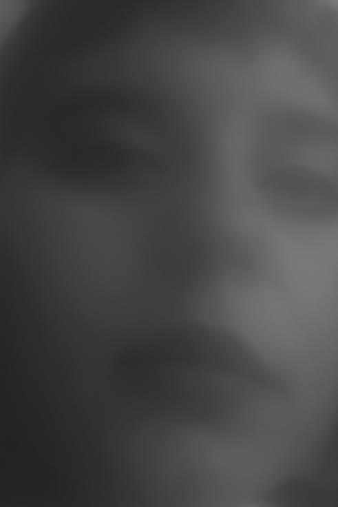Photo : Un visage androgyne en noir et blanc en contre-plongée montante, très flou. Un homme maquillé ? Une femme ? Un demi sourire, une expression lascive. Une connivence avec le spectateur..