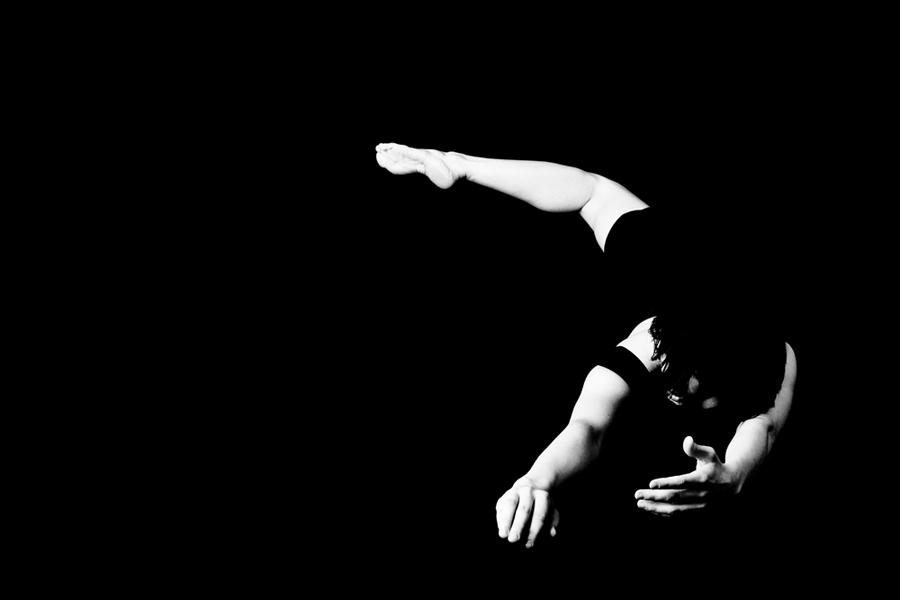 Photographie en noir et blanc : sur le fond noir de la photographie se détachent les membres blancs d'une silhouette en mouvement.