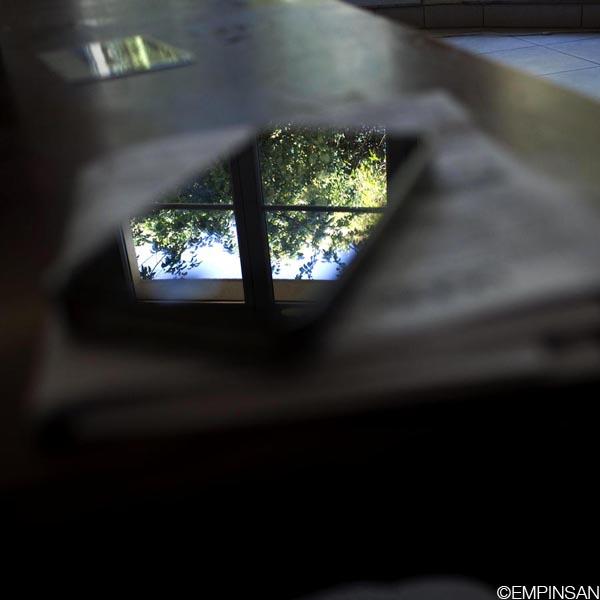 Photo couleur : sur une table, un smartphone. La table est floue, le smartphone est flou. Dans la vitre du smartphone se reflète une fenêtre derrière laquelle on voit un arbre vert et du ciel bleu. Le reflet est brillant, lumineux, très net. Un fort contraste avec le flou de la table et du smartphone.