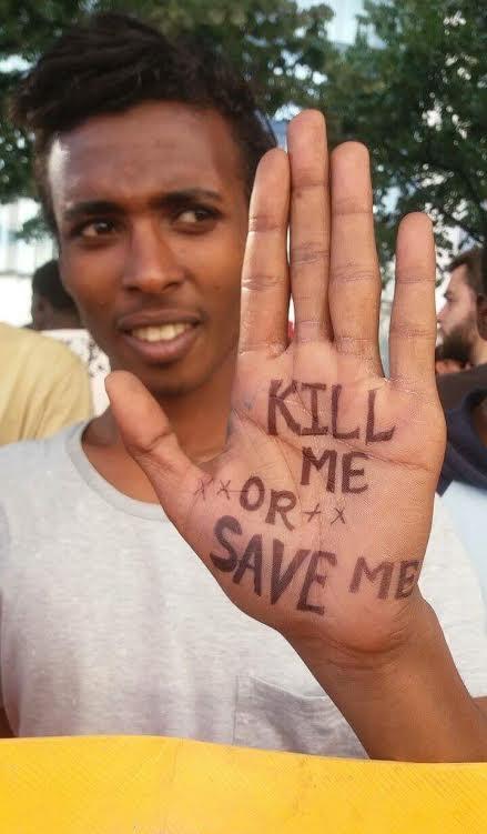 Photo couleur : Gadisa, jeune homme Éthiopien en T-shirt blanc fait face à la caméra en regardant de biais. Il tend la main gauche, paume vers l'avant : il y est écrit, au feutre : KILL ME OR SAVE ME.